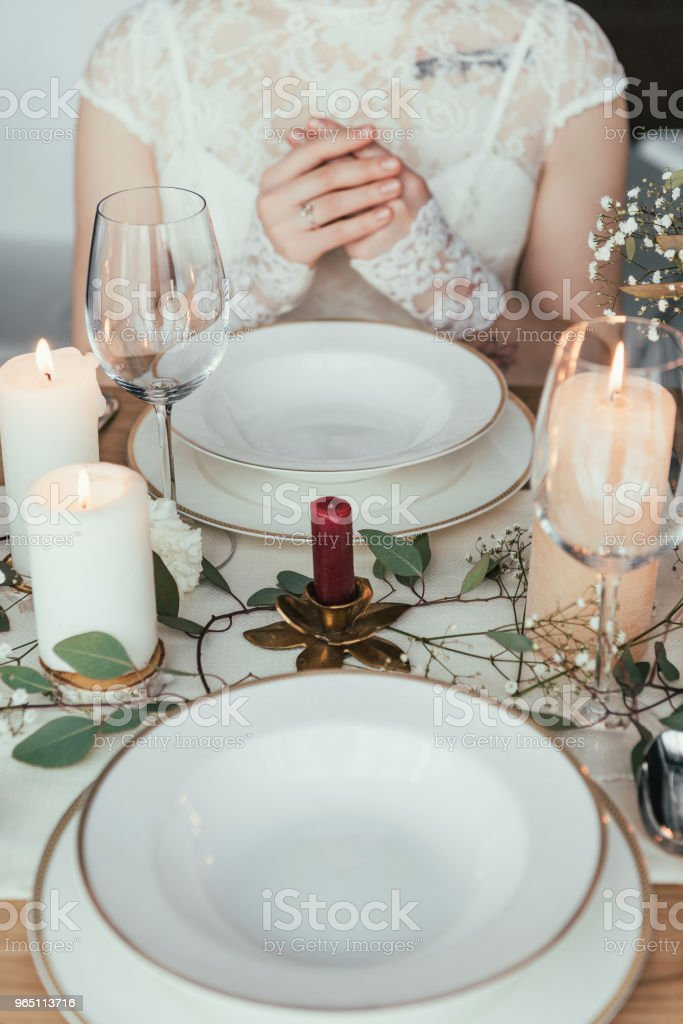 cropped shot of bride in white dress sitting at served table with empty plates and wineglasses, rustic wedding concept royalty-free stock photo