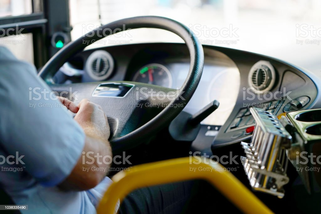 cropped shot of bus driver holding steering whee stock photo