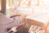 Hands of driver in a modern bus by driving.Concept - close-up of bus driver steering wheel and driving passenger bus. Toning