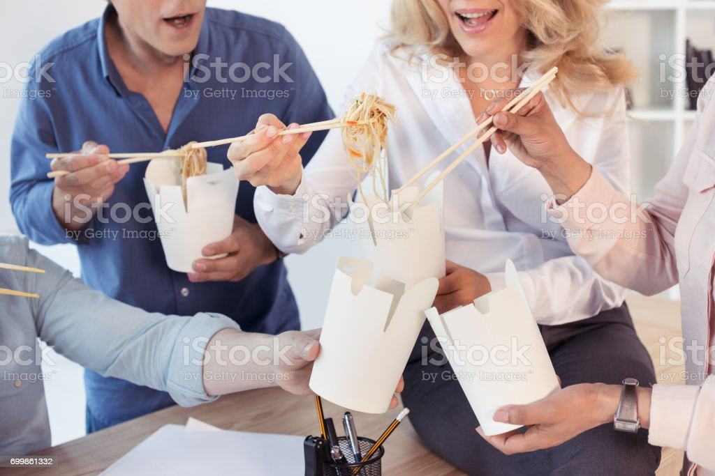 Cropped shot of business colleagues holding food boxes and eating asian food with chopsticks stock photo