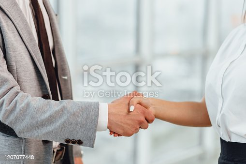 635949862 istock photo Cropped shot of business people shaking hands, greeting one another with successful deal and signing a contract. 1207077448
