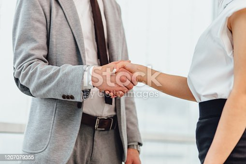 635949862 istock photo Cropped shot of business people shaking hands, greeting one another with successful deal and signing a contract. 1207079355