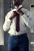 cropped shot of businessman in white shirt putting on his tie