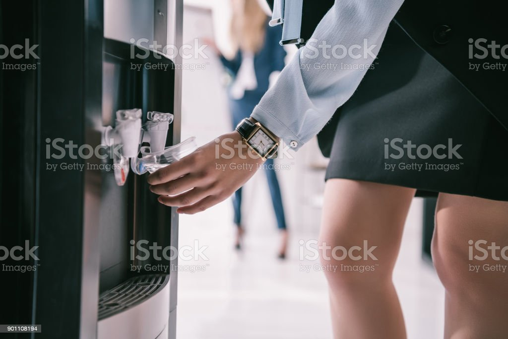 cropped shot of businesswoman pouring water from dispenser stock photo