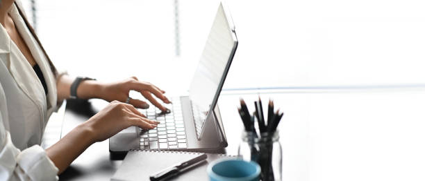 Cropped shot of businesswoman typing on keyboard of computer tablet at her work station. stock photo