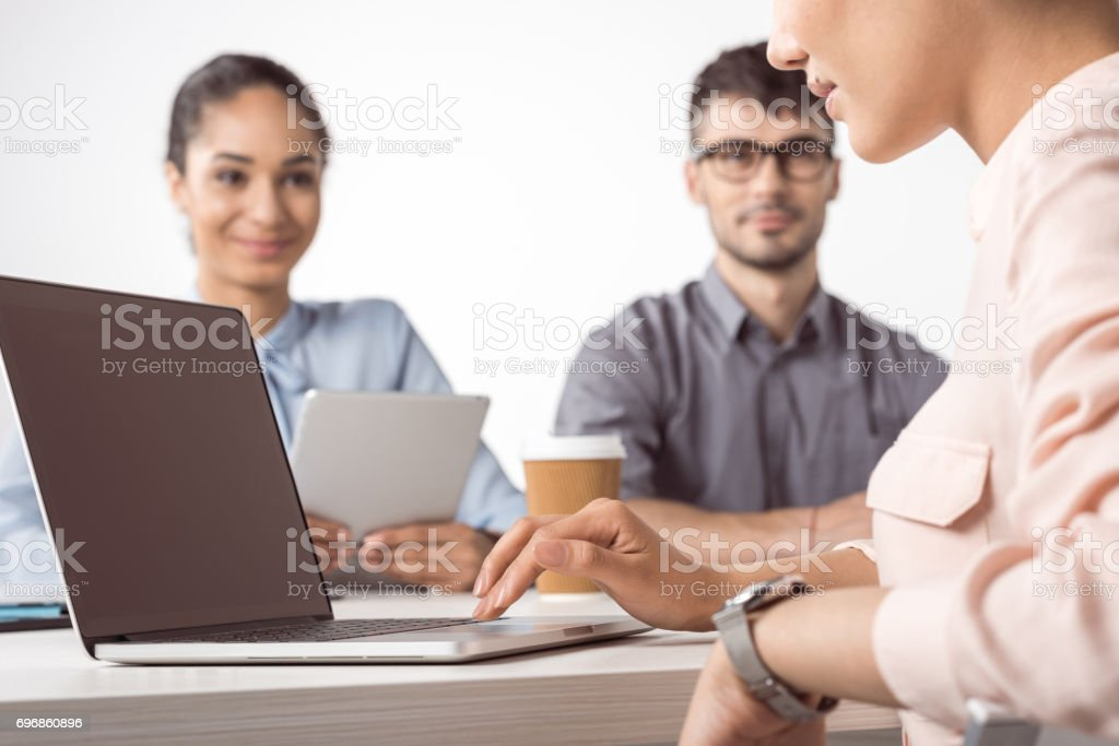 cropped shot of businesswoman using laptop while her colleagues sitting at table stock photo