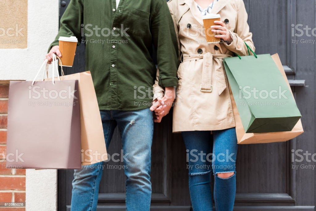 cropped shot of casual couple standing with shopping bags and drinking coffee on street stock photo