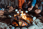 焚き火でマシュマロを焙煎カジュアルな友人のショットをトリミング