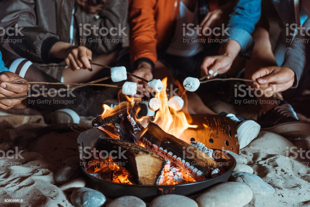 cropped shot of casual friends roasting marshmallows on bonfire stock photo