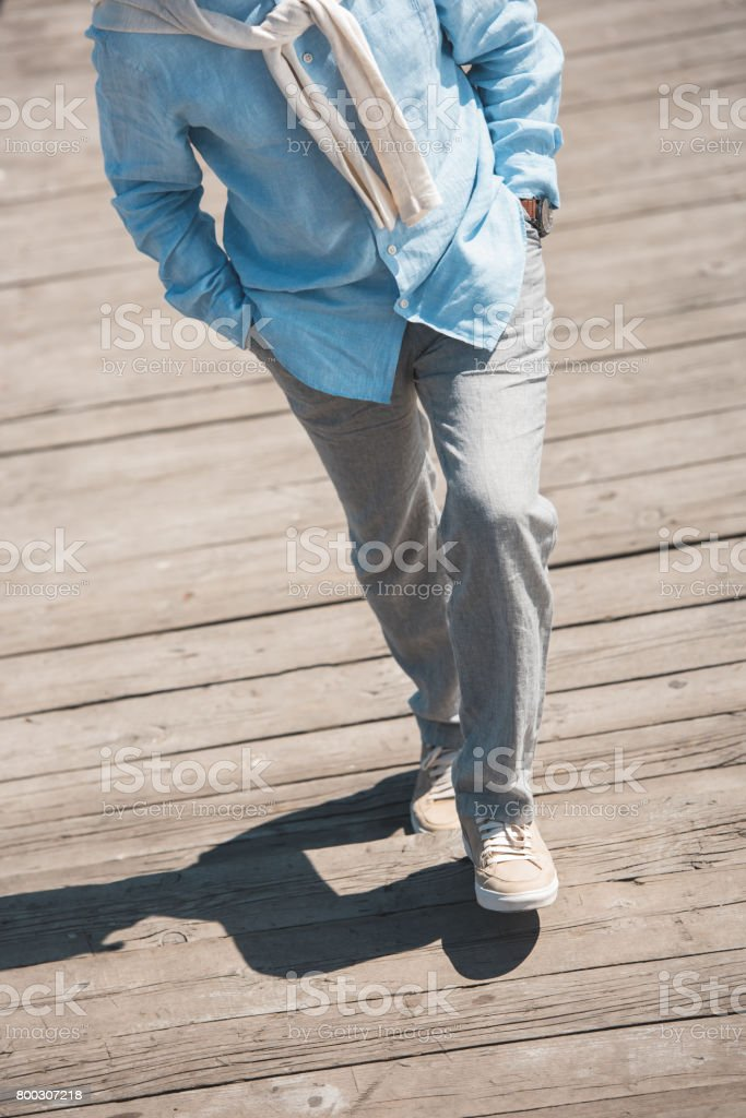 cropped shot of casual man walking by wooden pavement at daytime stock photo
