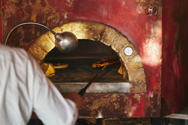 cropped shot of chef taking pizza from masonry oven at restaurant kitchen stock photo