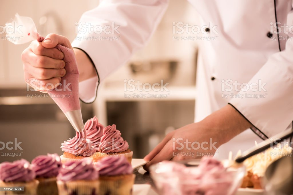 cropped shot of confectioner putting cream on cupcakes - Стоковые фото В помещении роялти-фри