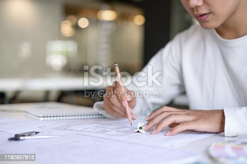 976560476 istock photo Cropped shot of creative Architect designing and sketching the building construction project at workplace. 1192607913