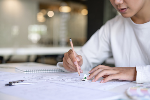 912867216 istock photo Cropped shot of creative Architect designing and sketching the building construction project at workplace. 1192607913