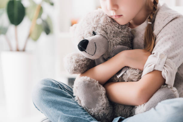 cropped shot of depressed little child embracing her teddy bear cropped shot of depressed little child embracing her teddy bear teddy bear stock pictures, royalty-free photos & images