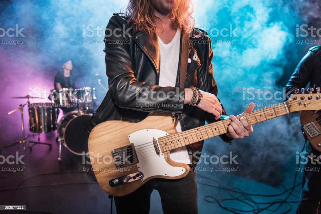 Cropped shot of electric guitar player playing hard rock music on stage stock photo