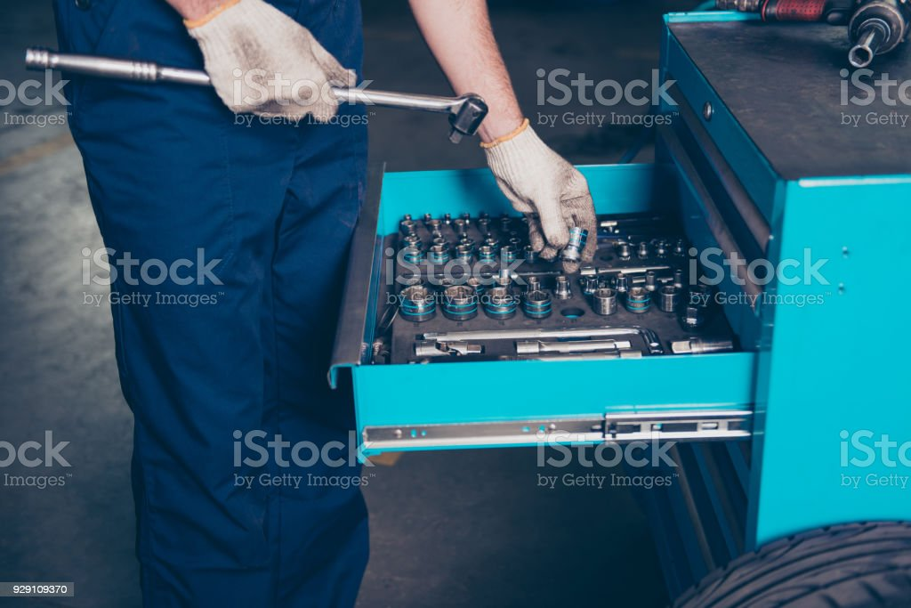 Cropped shot of engineer, hold roller clutch wrench, put or take bit with dirty gloves on shelf. Tap wrench and hexahedral adapters, fitting, tap, cap, chrome, steel, tubular, row of  options stock photo