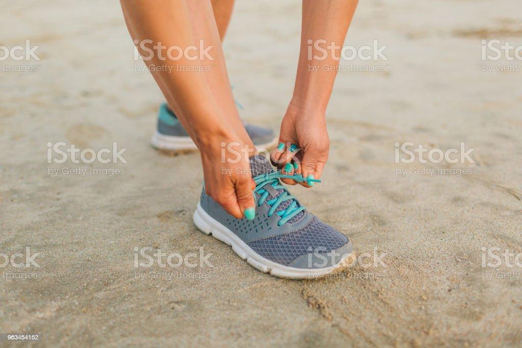 kadın atlet kumsalda ayakkabı bağcığı bağlama kadeh kırpılmış - Royalty-free Aktivite Stok görsel