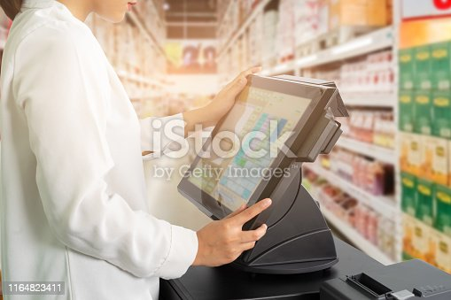Cropped shot of female cashier staff standing and working with POS or point of sale machine at counter in supermarket.