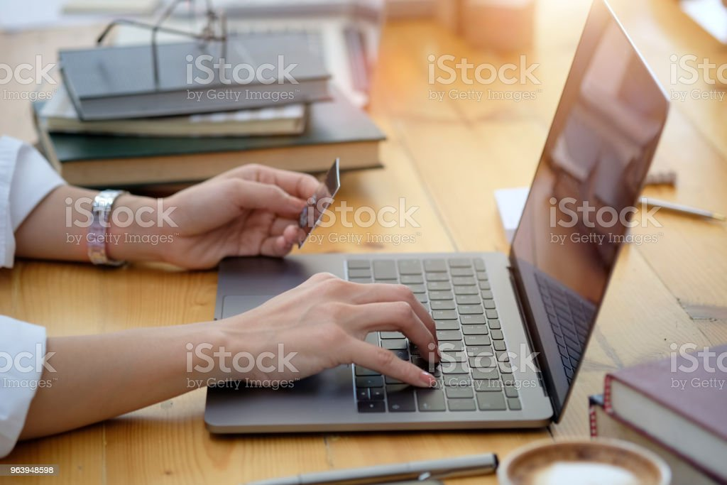 Cropped shot of female hand holding plastic credit card and using laptop. Online shopping payment concept. - Royalty-free Adult Stock Photo