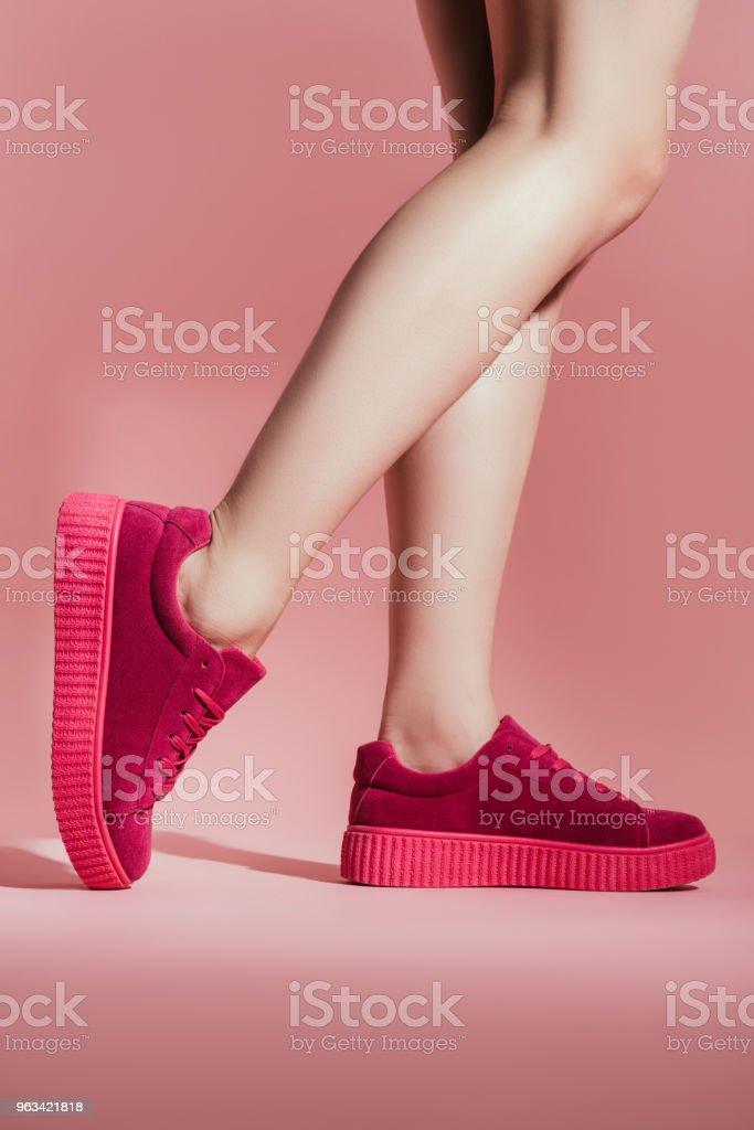 recadrée tir de fille en élégantes baskets sur fond rose - Photo de A la mode libre de droits