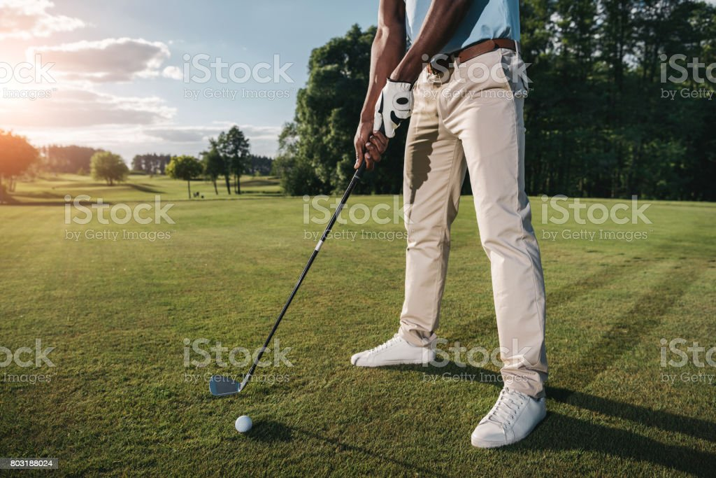 Cropped shot of golfer holding club and hitting ball on green grass stock photo