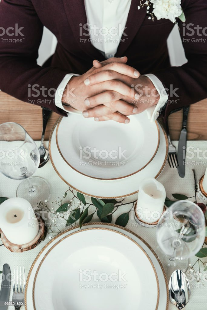 cropped shot of groom in suit sitting at served table, rustic wedding concept zbiór zdjęć royalty-free