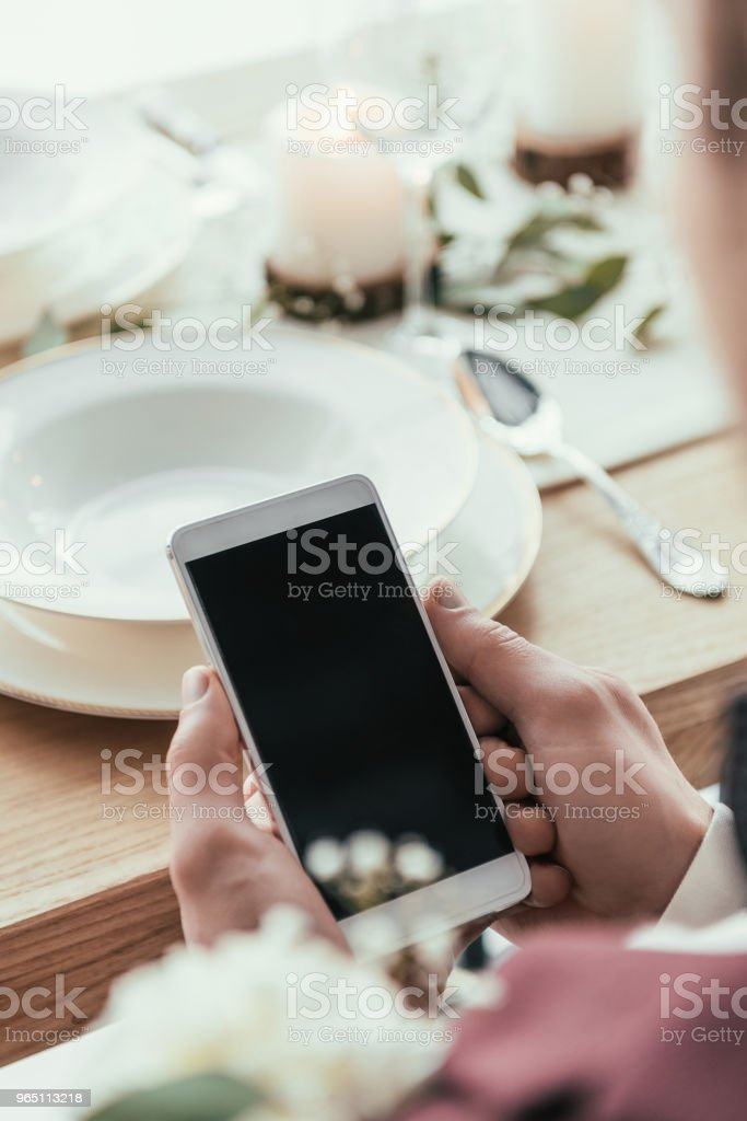 cropped shot of groom using smartphone at served rustic table zbiór zdjęć royalty-free