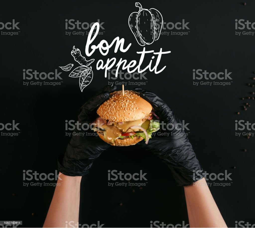 cropped shot of hands in gloves holding delicious burger with turkey, vegetables and caesar dressing on black with 'bon appetit' lettering stock photo