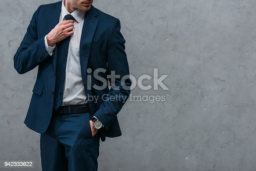 cropped shot of handsome businessman in stylish suit in front of concrete wall