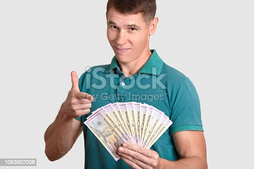 Cropped shot of handsome man holds lots of dollars, indicates at cash money, glad to earn much, being rich, dressed in casual t shirt, isolated over white background. Male with banknotes indoor