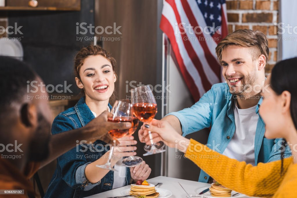 cropped shot of happy young multiethnic friends clinking wine glasses stock photo