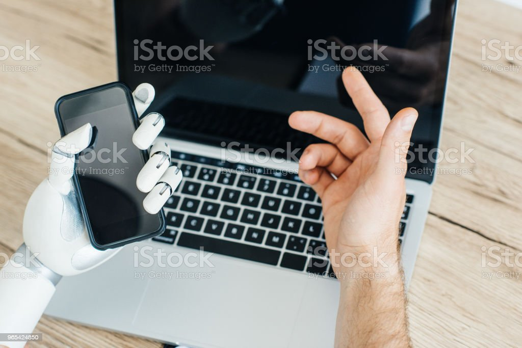 cropped shot of human and robot hands using smartphone and laptop with blank screens royalty-free stock photo