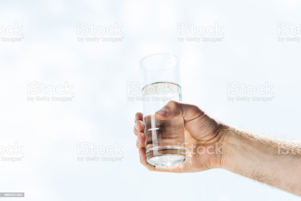 cropped shot of human hand holding glass of fresh water royalty-free stock photo
