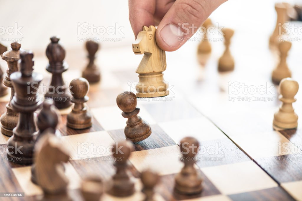 cropped shot of human hand playing chess, selective focus zbiór zdjęć royalty-free