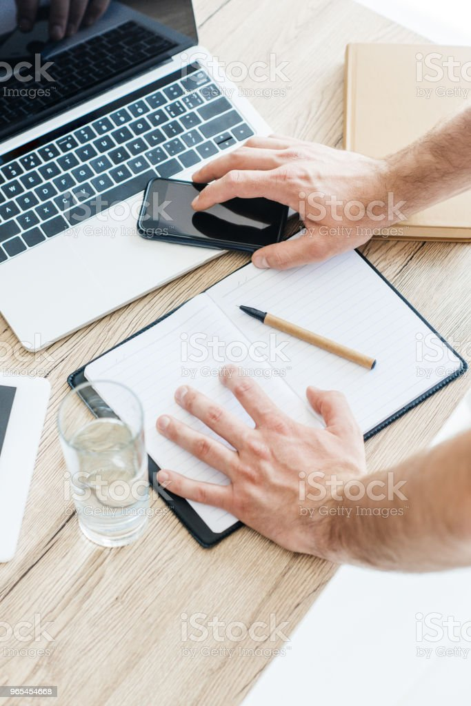cropped shot of human hands with smartphone, laptop and notebook at workplace royalty-free stock photo
