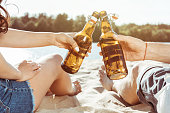 cropped shot of man and woman clinking bottles of beer while resting on beach