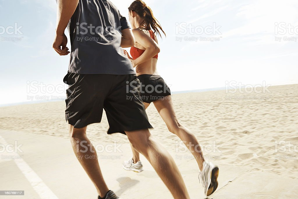 Cropped shot of man and woman running on beach stock photo