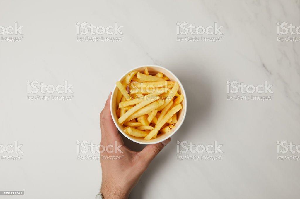 recadrée tir d'homme tenant le bol de délicieuses frites français sur blanc - Photo de Adulte libre de droits