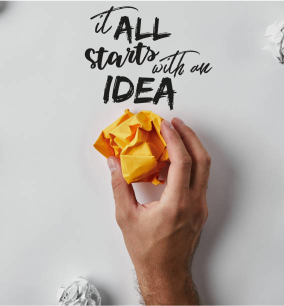 """cropped shot of man holding crumpled yellow paper with """"it all starts with an idea"""" inspiration on white surface - idea foto e immagini stock"""