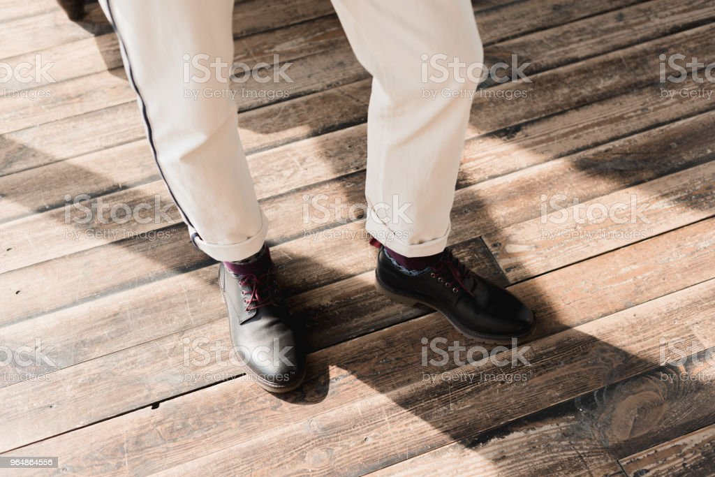 cropped shot of man in stylish shoes and pants standing on rustic wooden floor royalty-free stock photo