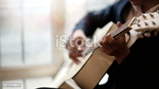Cropped shot of man practicing in playing acoustic guitar
