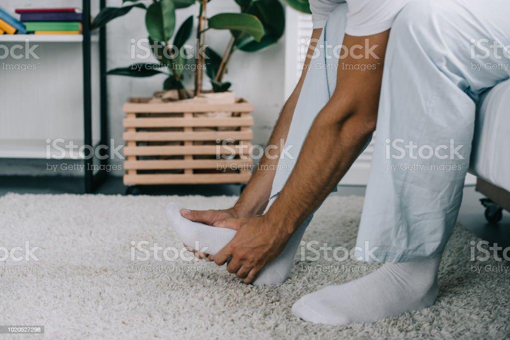 zugeschnittenen Schuss des Mannes am Bett sitzen und leiden unter Fußschmerzen – Foto