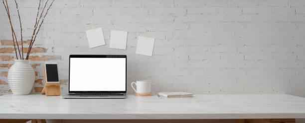 tiro cortado de espaço de trabalho mínimo com laptop maquete, smartphone, decorações e espaço de cópia - escrivaninha - fotografias e filmes do acervo