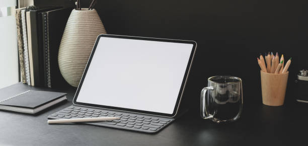 Cropped shot of modern workplace with blank screen tablet with office supplies with black wall