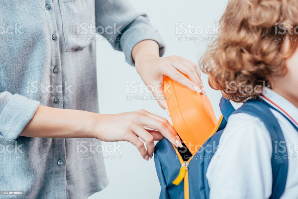 cropped shot of mother packing school lunch for son stock photo