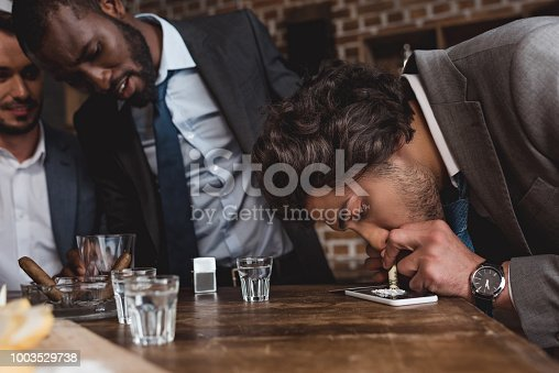 istock cropped shot of multiethnic businessmen looking at friend taking cocaine 1003529738