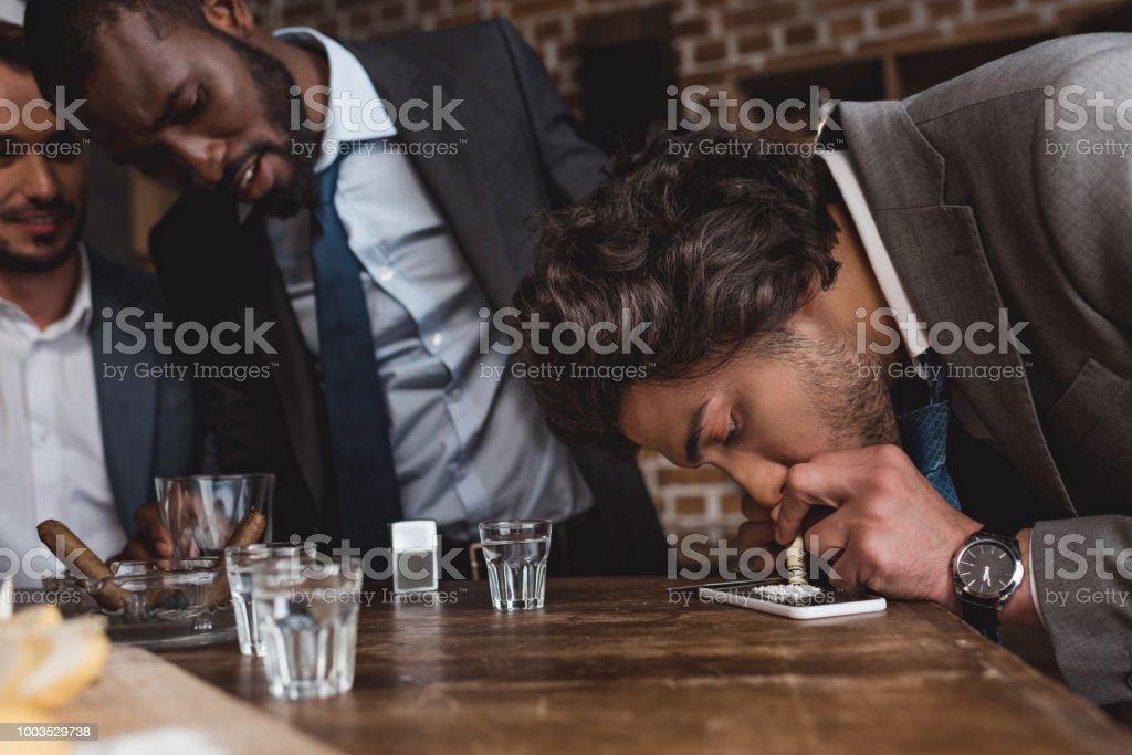 recadrée tir des hommes d'affaires multiethniques en regardant un ami prenant la cocaïne - Photo