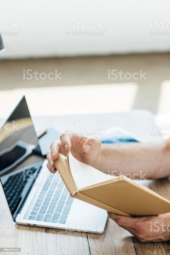 cropped shot of person holding book at table with laptop royalty-free stock photo