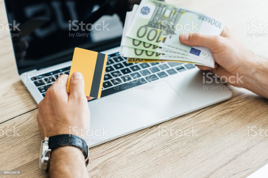 cropped shot of person holding credit card and euro banknotes above laptop zbiór zdjęć royalty-free